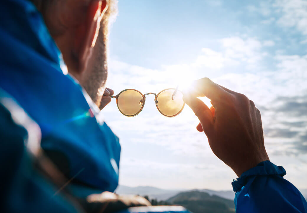 man holding sunglasses to sun