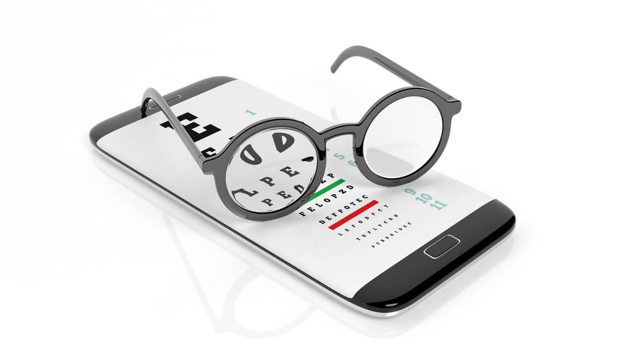 Glasses on phone screen with eye test