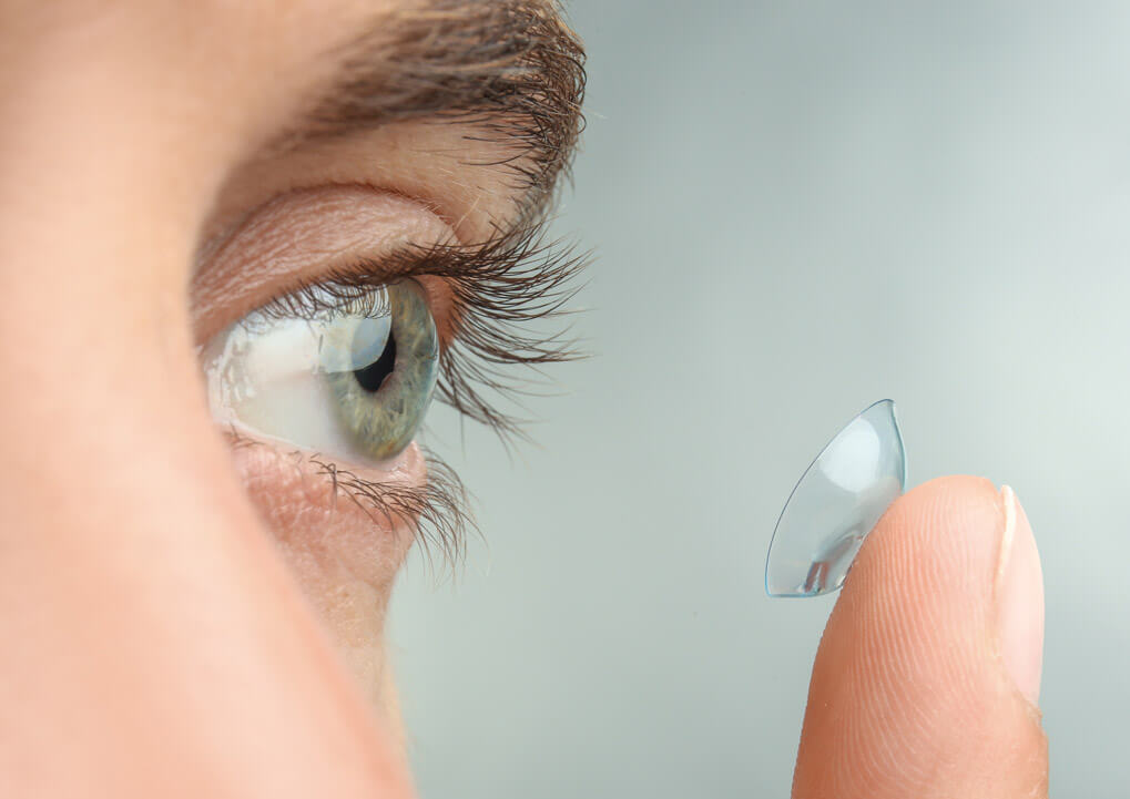 Man with contact lens on his finger