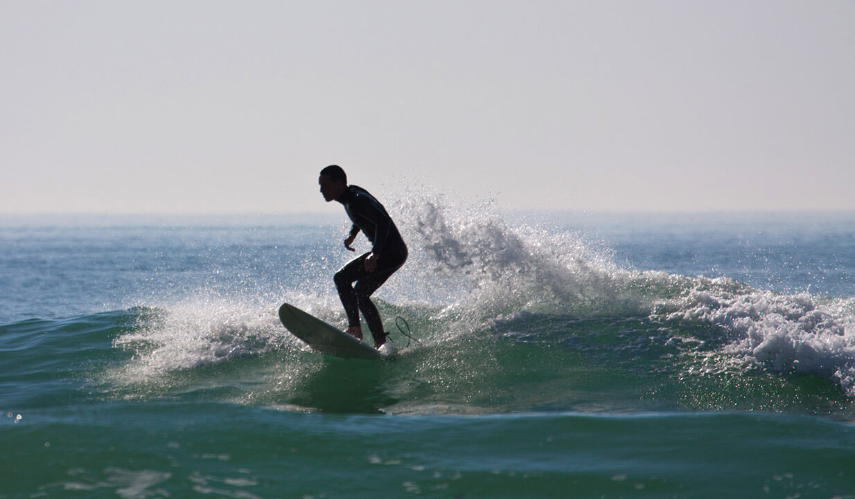 A silhouette of a man surfing