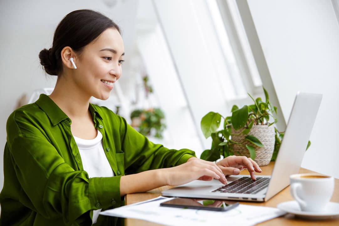 Woman using computer wearing green button down shirt